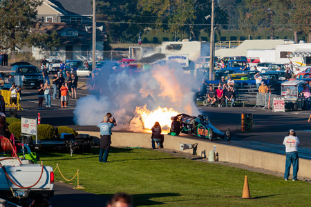 dragster: WOODBURN, OR - SEPTEMBER 27, 2015: Darin Bays Warped Speed Black Rat jet dragster blows fire and smoke towards spectators during the NHRA 30th Annual Fall Classic at the Woodburn Dragstrip.