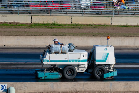 maching: WOODBURN, OR - SEPTEMBER 27, 2015: Worker on a track cleaning maching cleans the race surface after a crash at the NHRA 30th Annual Fall Classic at the Woodburn Dragstrip.