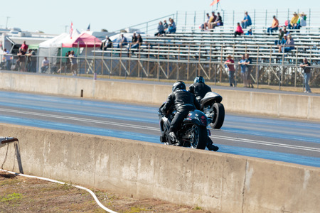 drag race: WOODBURN, OR - SEPTEMBER 27, 2015: Two motocycles racing down the track at the NHRA 30th Annual Fall Classic at the Woodburn Dragstrip. Editorial