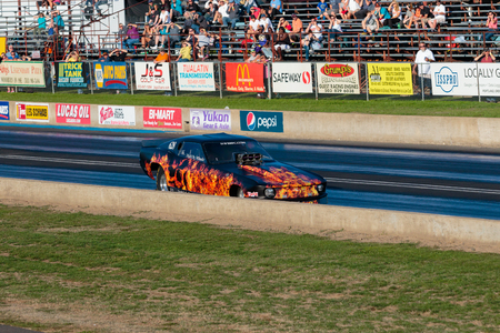 dragstrip: WOODBURN, OR - SEPTEMBER 27, 2015: Funny car Hell On Wheels crashes into the wall at the NHRA 30th Annual Fall Classic at the Woodburn Dragstrip.
