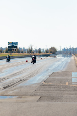 drag race: WOODBURN, OR - SEPTEMBER 27, 2015: Two motorcycles racing down the track at the NHRA 30th Annual Fall Classic at the Woodburn Dragstrip. Editorial