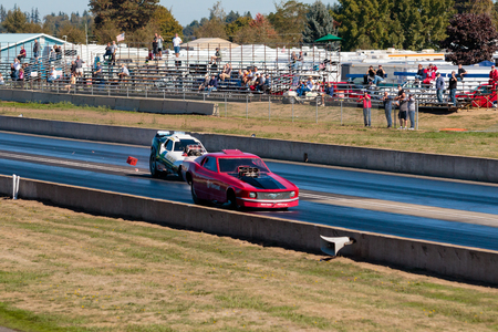 drag race: WOODBURN, OR - SEPTEMBER 27, 2015: Hart Braker funny car comes across the middle line during a semi-final race at the NHRA 30th Annual Fall Classic at the Woodburn Dragstrip.