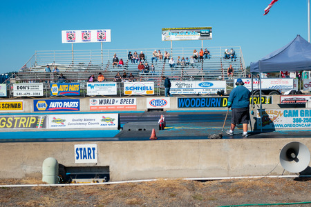 dragstrip: WOODBURN, OR - SEPTEMBER 27, 2015: Starting line worker mopping oil at the NHRA 30th Annual Fall Classic at the Woodburn Dragstrip.