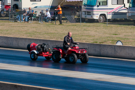 WOODBURN, OR - SEPTEMBER 27, 2015: Track worker drives an ATV with a drying machine on the back to dry the race surface at the NHRA 30th Annual Fall Classic at the Woodburn Dragstrip. Sajtókép