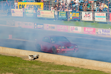 drag race: WOODBURN, OR - SEPTEMBER 27, 2015: Turbo boosted Ford Mustang performing a burnout at the NHRA 30th Annual Fall Classic at the Woodburn Dragstrip.
