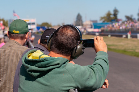 dragster: WOODBURN, OR - SEPTEMBER 27, 2015: Spectators with phones film a jet dragster at the NHRA 30th Annual Fall Classic at the Woodburn Dragstrip. Editorial
