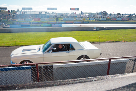 dragstrip: WOODBURN, OR - SEPTEMBER 27, 2015: White mustang passes by on the return track at the NHRA 30th Annual Fall Classic at the Woodburn Dragstrip.