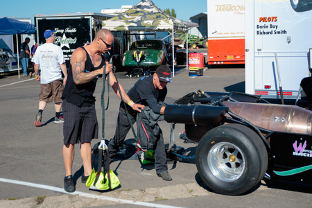 dragster: WOODBURN, OR - SEPTEMBER 27, 2015: Darin Bay and mechanic packing a parachute into their jet dragster for the Warped Speed team at the NHRA 30th Annual Fall Classic at the Woodburn Dragstrip.