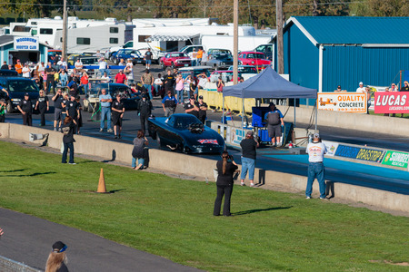 drag race: WOODBURN, OR - SEPTEMBER 27, 2015: Spectators and NHRA officials watch the starting line for a licensing run at the NHRA 30th Annual Fall Classic at the Woodburn Dragstrip. Editorial
