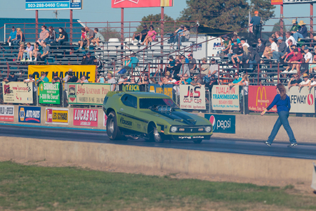 drag race: WOODBURN, OR - SEPTEMBER 27, 2015: Funny car being guided back to the starting line after performing a burnout at the NHRA 30th Annual Fall Classic at the Woodburn Dragstrip.