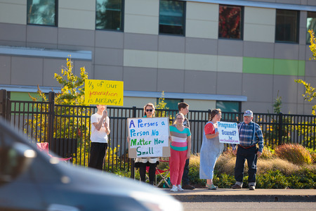 protesters: EUGENE, OR - OCTOBER 4, 2015: Anti-abortion protesters target pedestrian and vehicle passersby in front of Planned Parenthood of Southwestern Oregon located in Eugene. Editorial