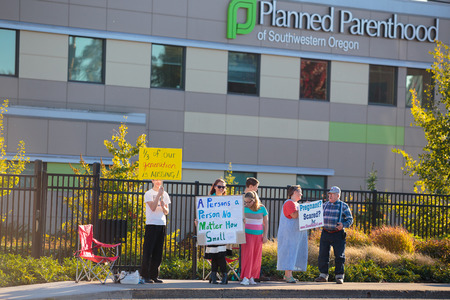 eugene: EUGENE, OR - OCTOBER 4, 2015: Anti-abortion protesters target pedestrian and vehicle passersby in front of Planned Parenthood of Southwestern Oregon located in Eugene. Editorial