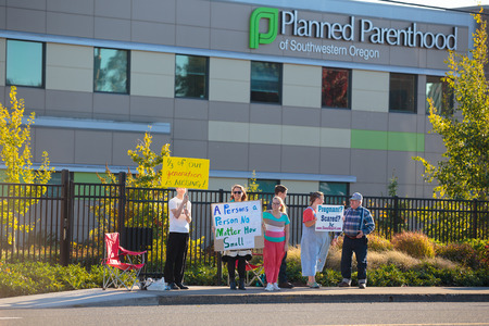 planned: EUGENE, OR - OCTOBER 4, 2015: Anti-abortion protesters target pedestrian and vehicle passersby in front of Planned Parenthood of Southwestern Oregon located in Eugene. Editorial