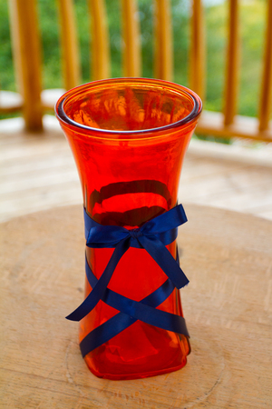 Red wedding vase at a reception outdoors.