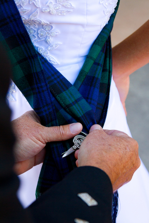 attire: Traditional Scottish wedding day attire of a kilt worn by the groom.