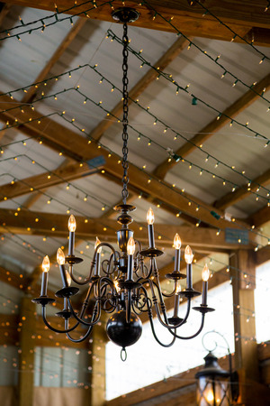 decor: Chandelier in black and metal at a wedding ceremony in a huge barn.