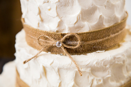 Wedding cake at a reception party in all white with burlap and bows.