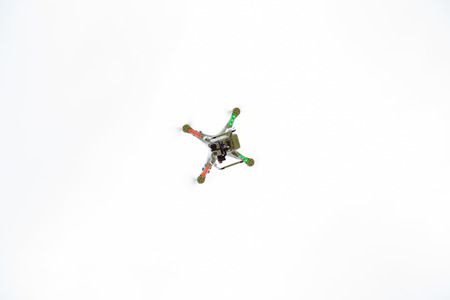quad: DALLAS, OR - JUNE 28, 2014: Phantom quad copter drone with Go Pro hero 3 camera connected flying above filming video.