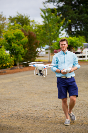 DALLAS, OR - JUNE 28, 2014: Male pilot flying a Phantom quad copter drone with Go Pro hero 3 camera connected filming video at a wedding. 新闻类图片