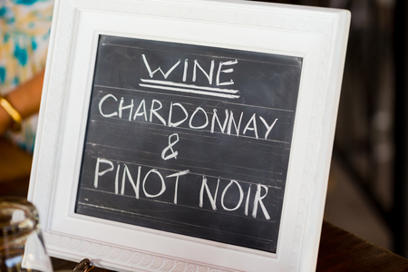 pinot noir: Sign showing the wine menu at a wedding recepiton in Southern Oregon includes chardonnay and pinot noir. Stock Photo