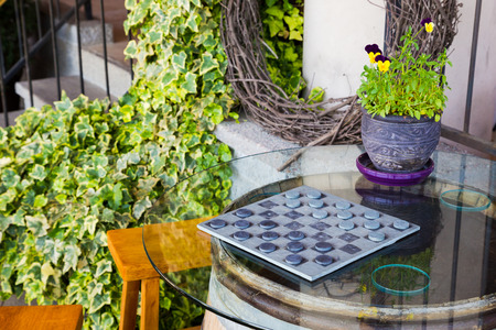 Wine barrel table with glass top plays host to this game of checkers.