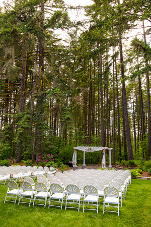 venue: Wedding venue in Oregon has natural trees and beautiful guest seating amidst tall trees.