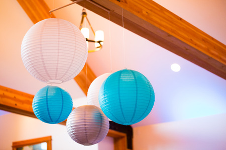 nuptials: Paper lanterns hung from the ceiling at a wedding reception indoors.