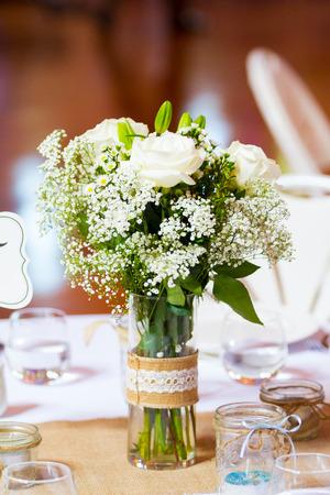 Middelpunt op een tafel op een bruiloft receptie met bloemen en couverts.