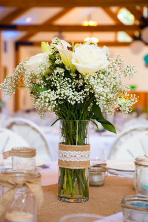floral decoration: Centerpiece on a table at a wedding reception with flowers and place settings.