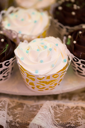 Cupcakes in vanilla and chocolate at a wedding reception dessert table.