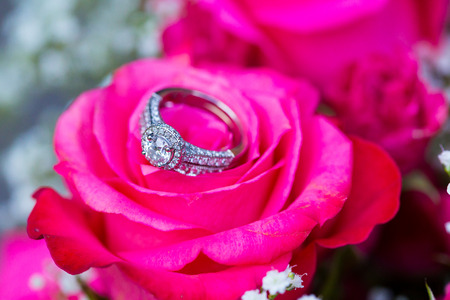 nuptials: Wedding rings for the bride and groom on flowers at a ceremony and reception.