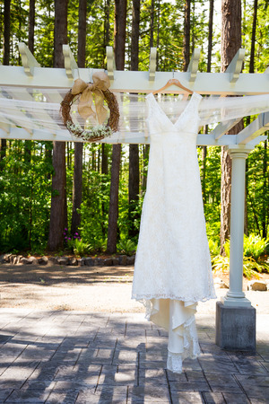 nuptials: Wedding dress of the bride hanging outdoors on a sunny day in Oregon.