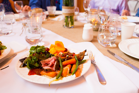 A sit down dinner for a wedding reception meal at a table.