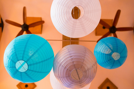 Paper lanterns hung from the ceiling at a wedding reception indoors.
