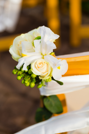 venue: Wedding decor of white flowers tied to the ceremony chairs at this outdoor venue.
