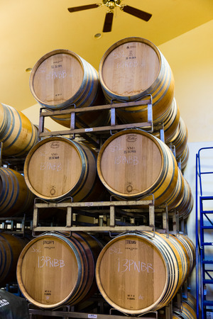 LORANE, OR - MAY 31, 2014: Wine barrels stacked together in the barrel room at Sweet Cheeks Winery.