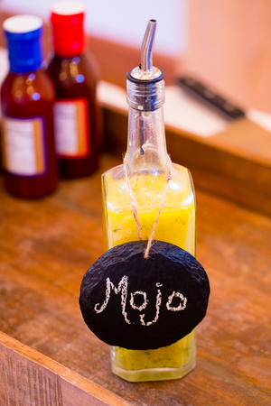 mojo: Bbq sauce with a yellow color and a label of mojo at a wedding reception catering bar. Stock Photo