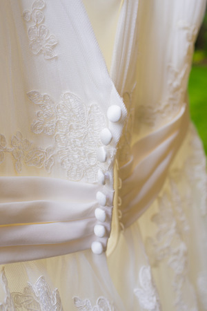 woman in dress: White wedding dress hanging outside before a ceremony.