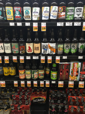ounce: SPRINGFIELD, OR - OCTOBER 22, 2015: Beer selection of 22 ounce bottles in a cooler at a grocery store.