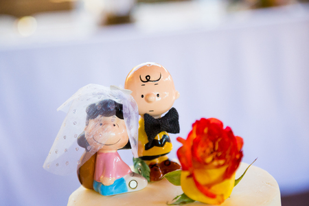 topper: SPRINGFIELD, OR - JULY 5, 2014: Charlie Brown Peanuts cake topper on a wedding cake at a reception.