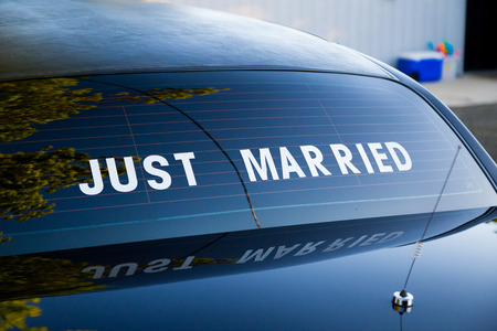 Just married sign on the back of a traditional black limo at a wedding.