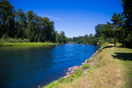 eugene: Springfield Oregons McKenzie River flows on the edge of town slowly with ample opportunity for intertubing recreation. Stock Photo