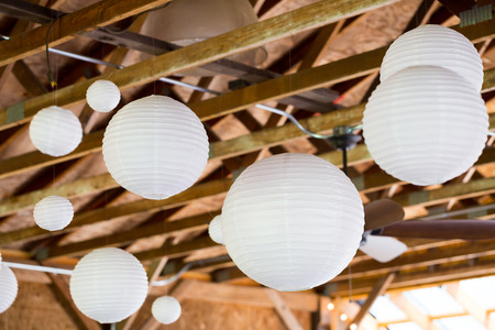 barn: White Chinese paper lanterns hung in a barn as diy wedding reception decor.