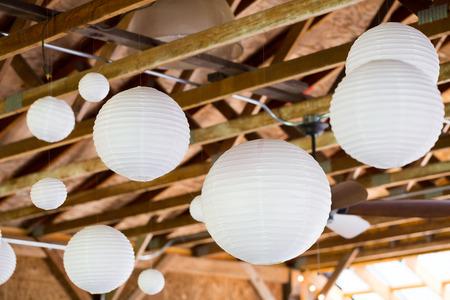lantern: White Chinese paper lanterns hung in a barn as diy wedding reception decor.