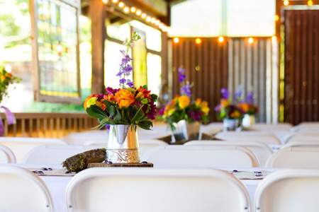 floral decoration: Wedding diy centerpieces on tables at a reception of orange and green flowers.