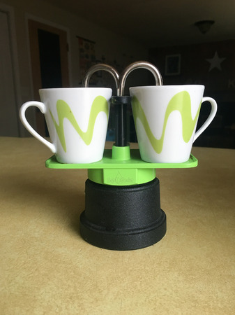 Stovetop espresso maker with two small cups for shots in green and white. Stock Photo