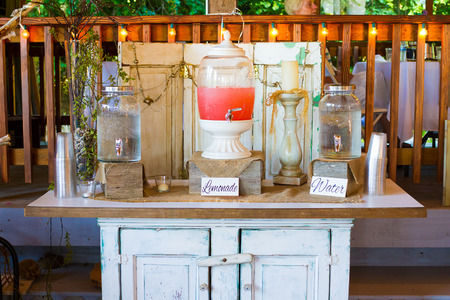 Pink lemonade stand at a wedding reception offers drinks for the guests.