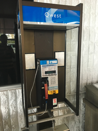 pay phone: SPRINGFIELD, OR - OCTOBER 28, 2015: Qwest pay phone at a store with a yellow pages DEX book hanging below.