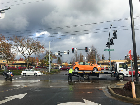 SPRINGFIELD, OR - OCTOBER 28, 2015: Tow truck has a vehicle on it after a traffic accident at a large intersection. Editorial