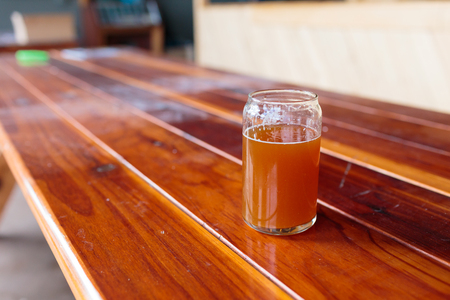 ipa: IPA in a beer glass on a wood table at a brewery restaurant. Stock Photo